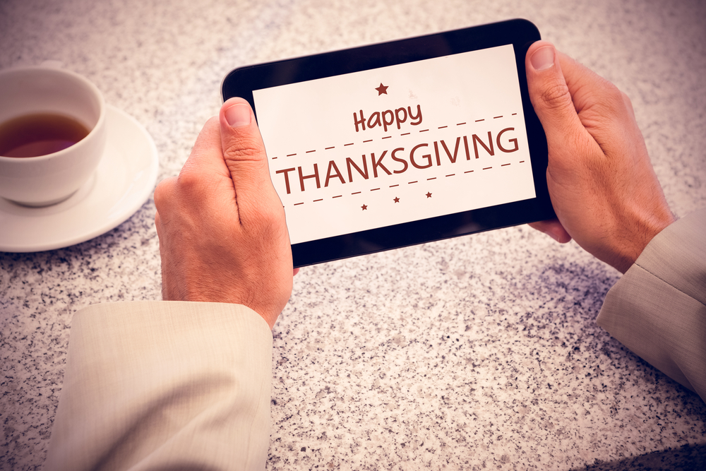 Businessman holding small tablet at table against happy thanksgiving